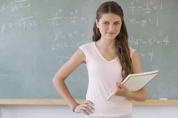 Girl standing in front of blackboard